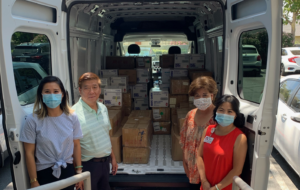The Chan family stands in front of a UHAUL moving van full of PPE they have donated