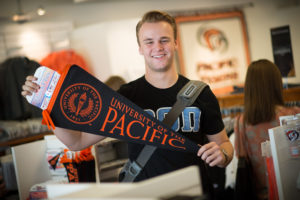 Smiling student holding Pacific pennant